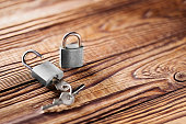 metal padlock with silvered keys on old wooden background. Estate and security concept with symbol of protection.