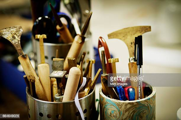 Metal pots full of hand tools for skilled work, for book binding tasks.