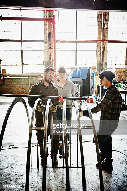 Metal shop owner and apprentices measuring project