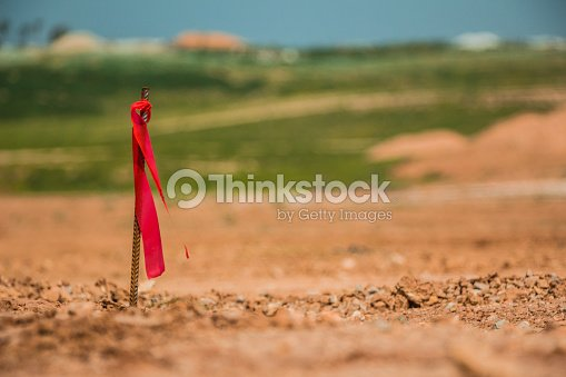 Metal survey peg with red flag on construction site : Stock Photo