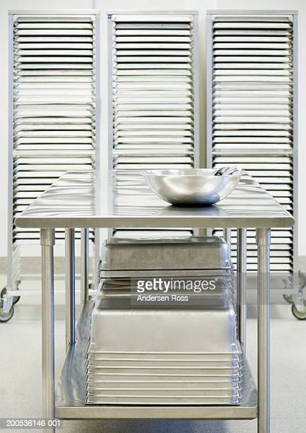 Metal table, bowl and trays in prep area of commercial kitchen