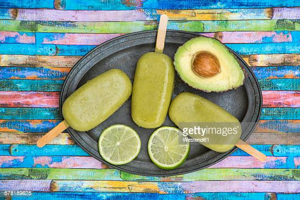 Metal tray of avocado ice lollies, avocado and slices of lime