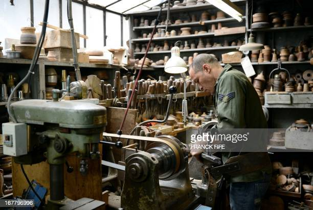 A metal turner and chiseler silversmith works the sheet of silver needed to make the 'Coupe des Mousquetaires' in Paris on April 30 2013 in the...