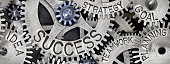 Macro photo of tooth wheel mechanism with SUCCESS concept related words imprinted on metal surface