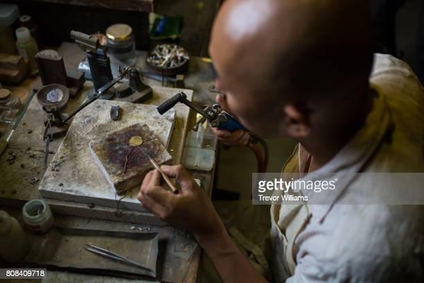 Metal worker and jeweller working in his workshop