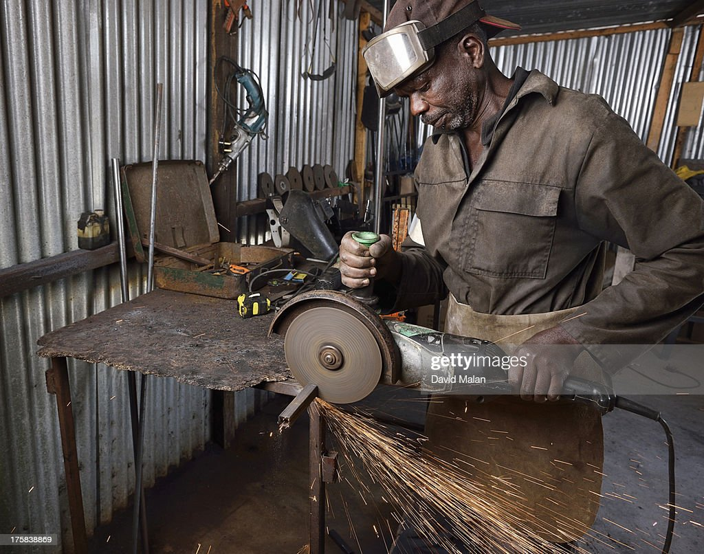 Metal worker using an angle grinder in his workshop. Philippi, Cape Town, South Africa.