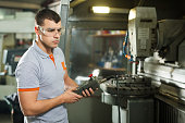 Metal Worker Working On CNC Machine In Factory