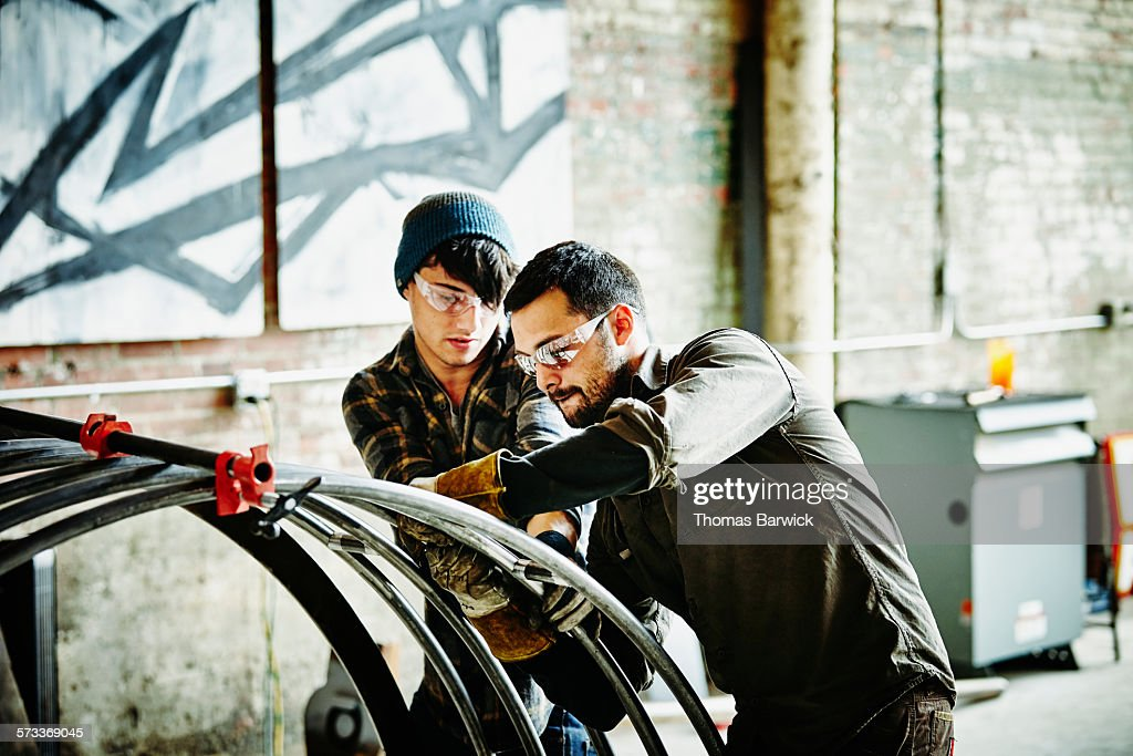 Metal workers adjusting support bars on project : Stock Photo