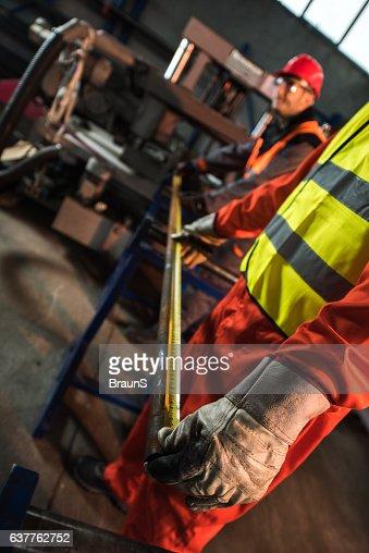 Metal workers measuring steel in an aluminum mill.