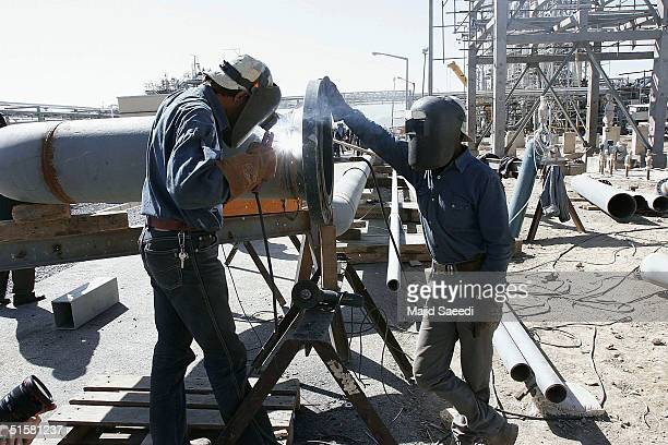 Metal workers weld together sections of Irans controversial heavy water production facility October 27 2004 at Arak south of the Iranian capital...