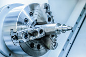 Chuck lathe closeup. Toned image in the cold industrial color.Shallow depth of field.