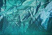 Green sequin, metallic fabric texture background.