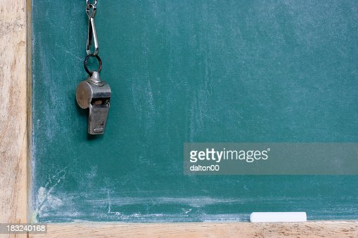 A metallic whistle hanging by the chalkboard