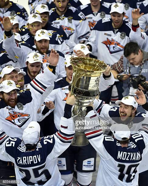 Metallurg Magnitogorsk team members celebrate as they hold the trophy of the Kontinental Hockey League after winning the final match against CSKA...