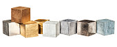 Metal cubes in a row, isolated on white. From left, tin,copper,brass,brass,aluminium,lead,iron and zinc.