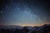 Meteor and milky way above snowy mountain