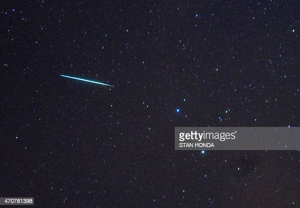 A meteor from the Geminids meteor shower enters the Earth's atmosphere past the stars Castor and Pollux on December 12 2009 above Southold New York...