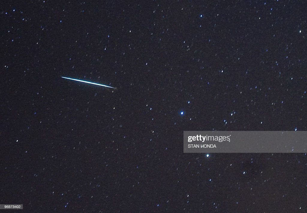 A meteor (L) from the Geminids meteor shower enters the Earth's atmosphere past the stars Castor and Pollux (two bright stars, R) on December 12, 2009 above Southold, New York. This meteor shower gets the name 'Geminids' because it appears to radiate from the constellation Gemini. Geminids are pieces of debris from an asteroid called 3200 Phaethon. Earth runs into a stream of debris from the object every year in mid-December, causing the meteors. The peak of the shower is expected the night of December 13-14 at about 0500 GMT on December 14. AFP PHOTO/Stan Honda