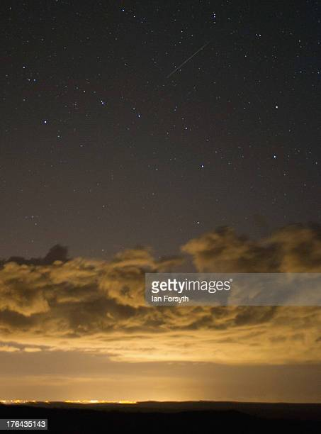 A meteor is visible as it streaks across the night sky and appearing to be above the constellation of Ursa Major on August 13 2013 over the North...