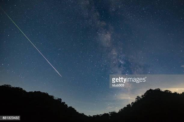 Un météore tire dans le ciel du ciel nocturne laissant une traînée de lumière à travers la voie lactée