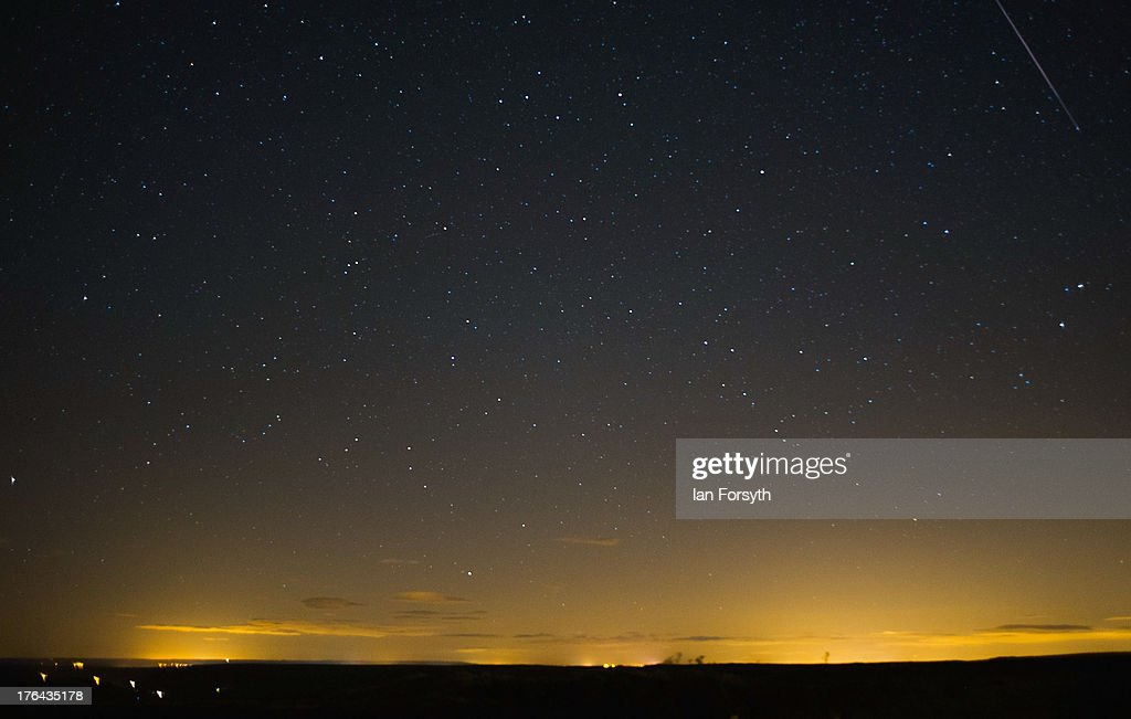 A meteor (top right) streaks across the night sky on August 13, 2013 over the North Yorkshire Moors, United Kingdom. The Perseid Meteor shower is visible from mid-july each year with peak activity being between the 9th and 14th of August. During the peak, the rate of meteors can reach 60 or more per hour. They can be seen all across the sky as they gradually fall away from the tail of the Swift-Tuttle comet.