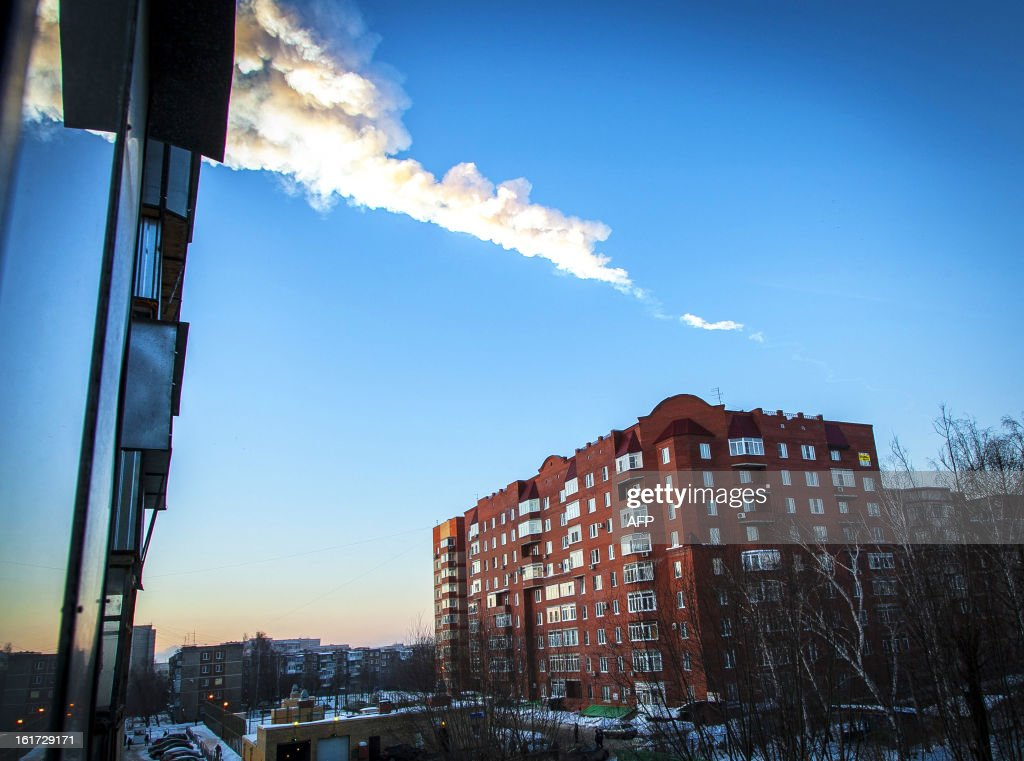 A meteorite trail is seen above a residential apartment block in the Urals city of Chelyabinsk, on February 15, 2013. A heavy meteor shower rained down today on central Russia, sowing panic as the hurtling space debris smashed windows and injured dozens of stunned locals, officials said. AFP PHOTO / 74.RU/ OLEG KARGOPOLOV