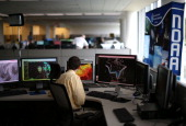 Meteorologist Jim Fracasso monitors weather in NOAA's Center for Weather and Climate Prediction July 2 2013 in Riverdale Maryland NOAA's National...