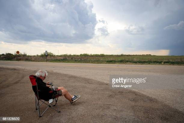 Meteorologist Josh Wurman president and founder of the Center For Severe Weather Research sits in a lawn chair as he scans radar on his smartphone...