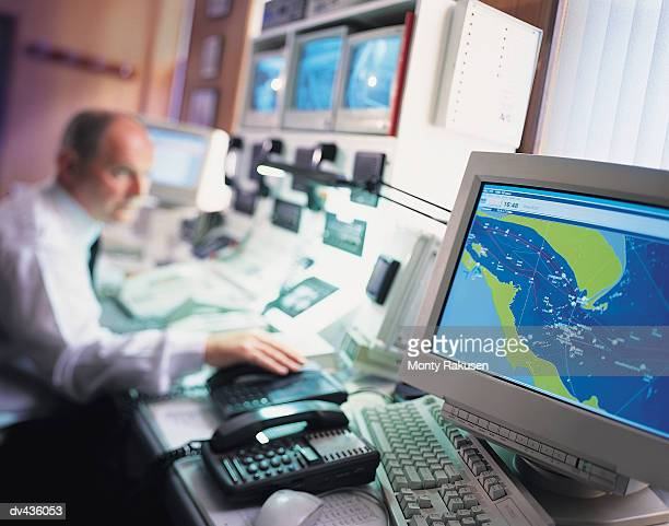 Meteorologist studying weather pattern on computer screens