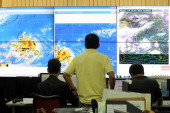 Meteorologists monitor the movement of typhoon Rammasun at the Philippine Atmospheric Geophysical and Astronomical Services Administration in Manila...