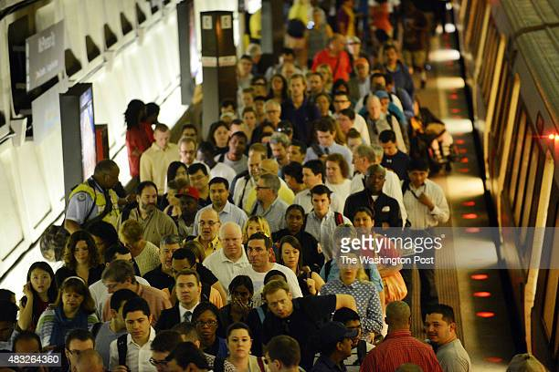 Metro commuters are forced to get off the train at McPierson Square Metro stop during severe service interruptions after a train derails during early...