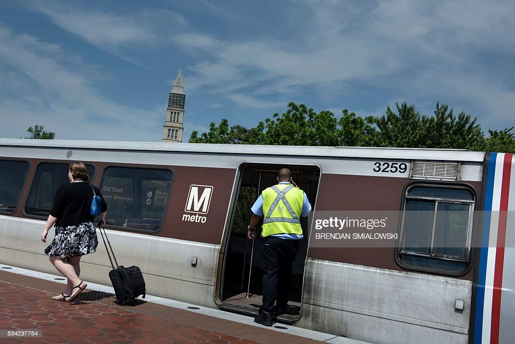 A Metro employee boards a train on the Blue and Yellow line in the Metro transit system May 25, 2016 in Alexandria, Virginia. / AFP / Brendan Smialowski