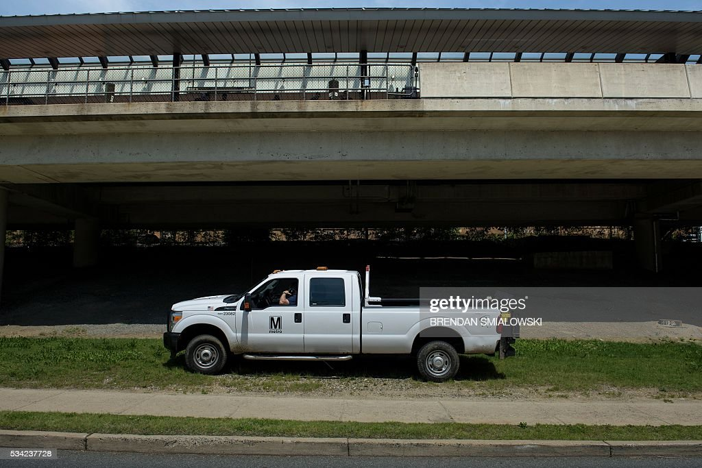 A Metro employee is seen talking on the phone outside a station in the Metro transit system May 25, 2016 in Alexandria, Virginia. / AFP / Brendan Smialowski