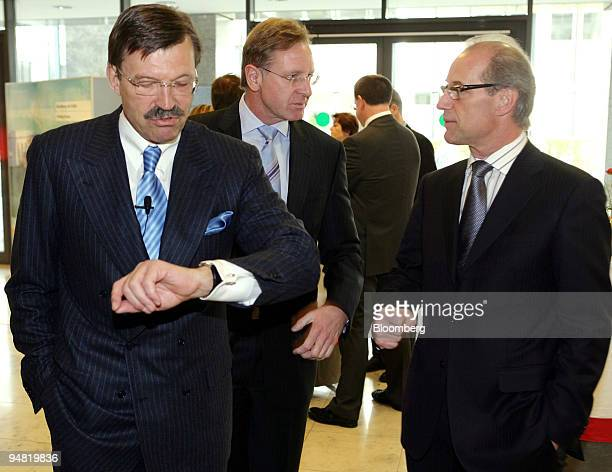 Metro Group Chief Executive HansJoachim Koerber left looks at his watch prior to a news conference in Duesseldorf Germany Wednesday March 22 2006...