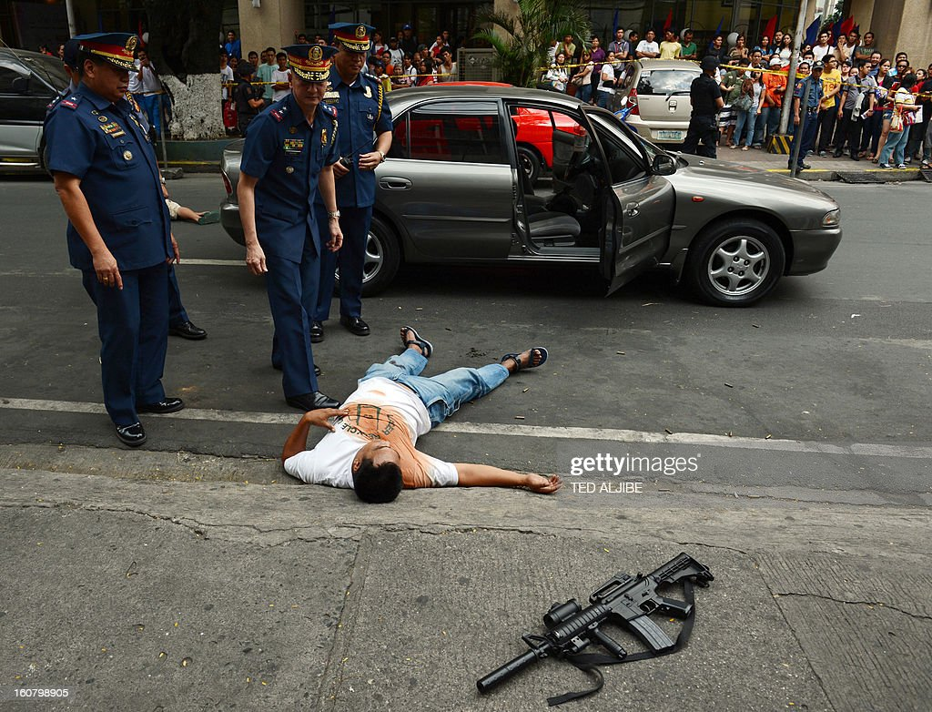 Metro Manila police chief Leonardo Espina (C) and Manila city district police chief Alex Gutierrez (L) inspect a 'crime scene' during a shopping mall robbery simulation in Manila on February 6, 2013, as part of heightened security and police visibility after recent attacks at shopping centres. Police have stepped up their visibility and security in response to recent attacks in popular Manila shopping malls, including the ransacking of a mall jewellery store on January 26.