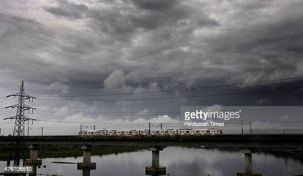Metro train passes as dense clouds hover over the skyline during the monsoon on July 6 2015 in New Delhi India