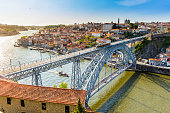 Metro rail seen travelling accross the Dom Luis I bridge that lies over river Douro in Porto city. This is a popular tourist destination and declared a UNESCO world heritage site. The cityscape seen o