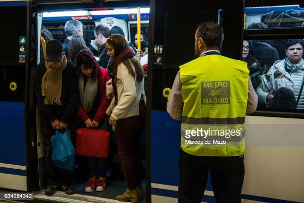 A metro worker acting like a 'metro pusher' as a large number of people attend to Avenida de America station due to the closure of line 8