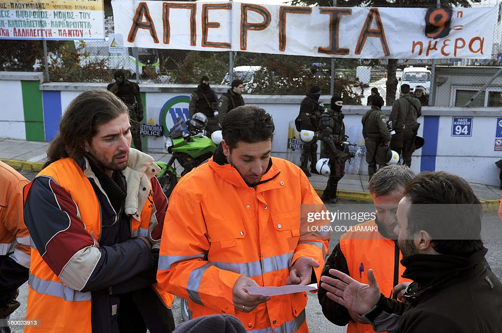 Metro workers read requisition forms as Greek riot police block the access to the main Athens metro depot on January 25, 2013 to break up a sit-in by striking workers. The raid on the centre, which strikers protesting austerity measures had occupied took place overnight. The government had ordered a civil mobilisation the day before to force the Athens metro staff to halt their strike, which has disrupted traffic in the Greek capital for over a week. Unions reacted by calling a general transport standstill today.