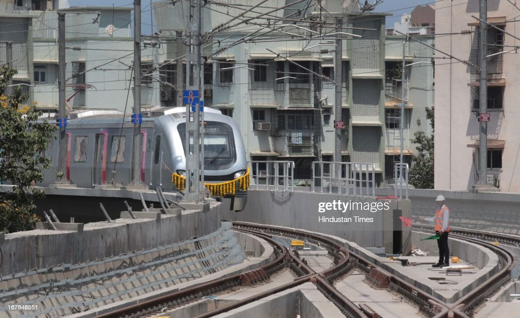 Metro zooms past the building in its first successful run at Versova, Andheri West on May 1, 2013 in Mumbai, India. Maharashtra's first Metro from Versova to Airport Road in Mumbai will be commissioned in September.