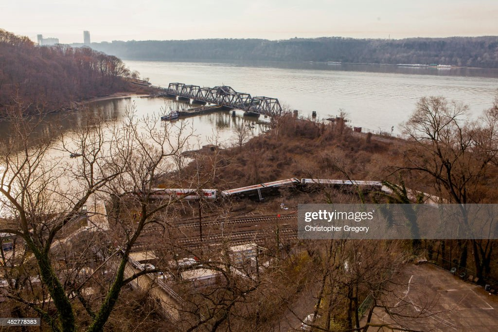 A Metro-North commuter train lies in the brush near the Hudson River after it derailed just north of the Spuyten Duyvil station December 1, 2013 in the Bronx borough of New York City. Multiple injuries and at least 4 deaths were reported after the seven car train left the tracks as it was heading to Grand Central Terminal along the Hudson River line.