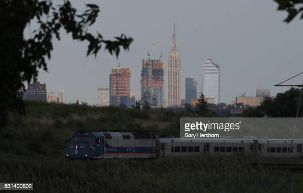 MetroNorth train moves past the skyline of midtown Manhattan and the Empire State Building in New York City on August 11 2017 as seen from Richard W...