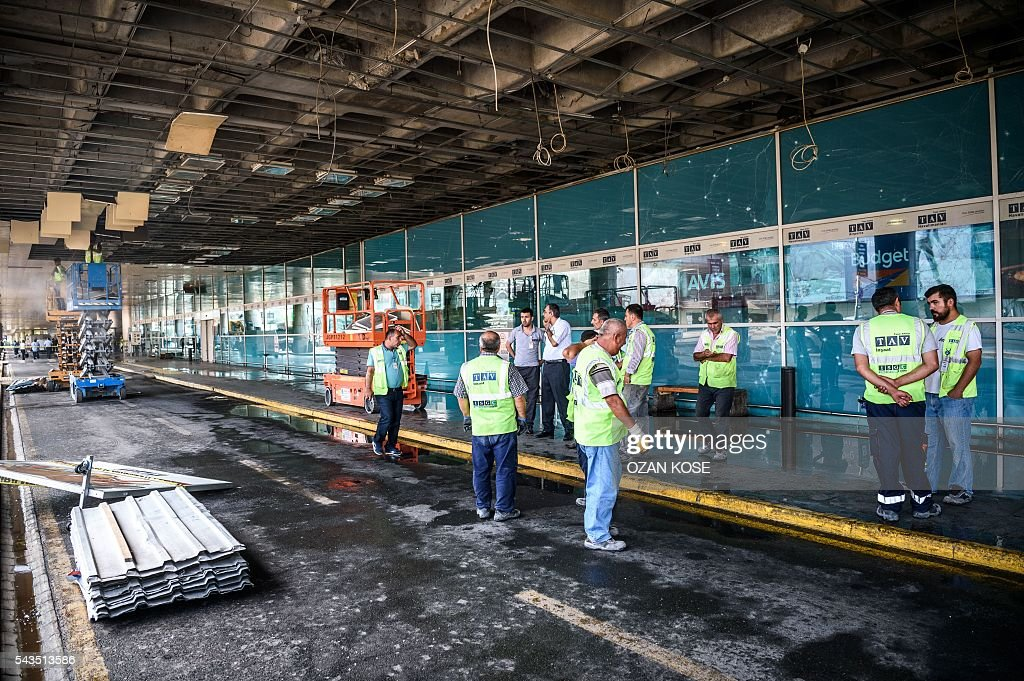 Metropolitan municipal employees and airport employees work in the cordoned off area at Ataturk airport's International airport on June 29, 2016, a day after a suicide bombing and gun attack targeted Istanbul's airport, killing at least 36 people. A triple suicide bombing and gun attack that occurred on June 28, 2016 at Istanbul's Ataturk airport has killed at least 36 people, including foreigners, with Turkey's prime minister saying early signs pointed to an assault by the Islamic State group. / AFP / OZAN