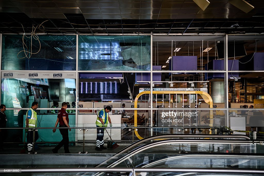 Metropolitan municipal employees and airport employees work to clear debris in the cordoned off area at Ataturk airport's International airport on June 29, 2016, a day after a suicide bombing and gun attack targeted Istanbul's airport, killing at least 36 people. A triple suicide bombing and gun attack that occurred on June 28, 2016 at Istanbul's Ataturk airport has killed at least 36 people, including foreigners, with Turkey's prime minister saying early signs pointed to an assault by the Islamic State group. / AFP / OZAN