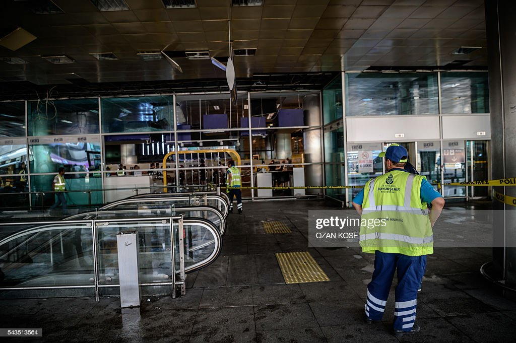 Metropolitan municipal employees work in the cordoned off area at Ataturk airport's International airport on June 29, 2016, a day after a suicide bombing and gun attack targeted Istanbul's airport, killing at least 36 people. A triple suicide bombing and gun attack that occurred on June 28, 2016 at Istanbul's Ataturk airport has killed at least 36 people, including foreigners, with Turkey's prime minister saying early signs pointed to an assault by the Islamic State group. / AFP / OZAN