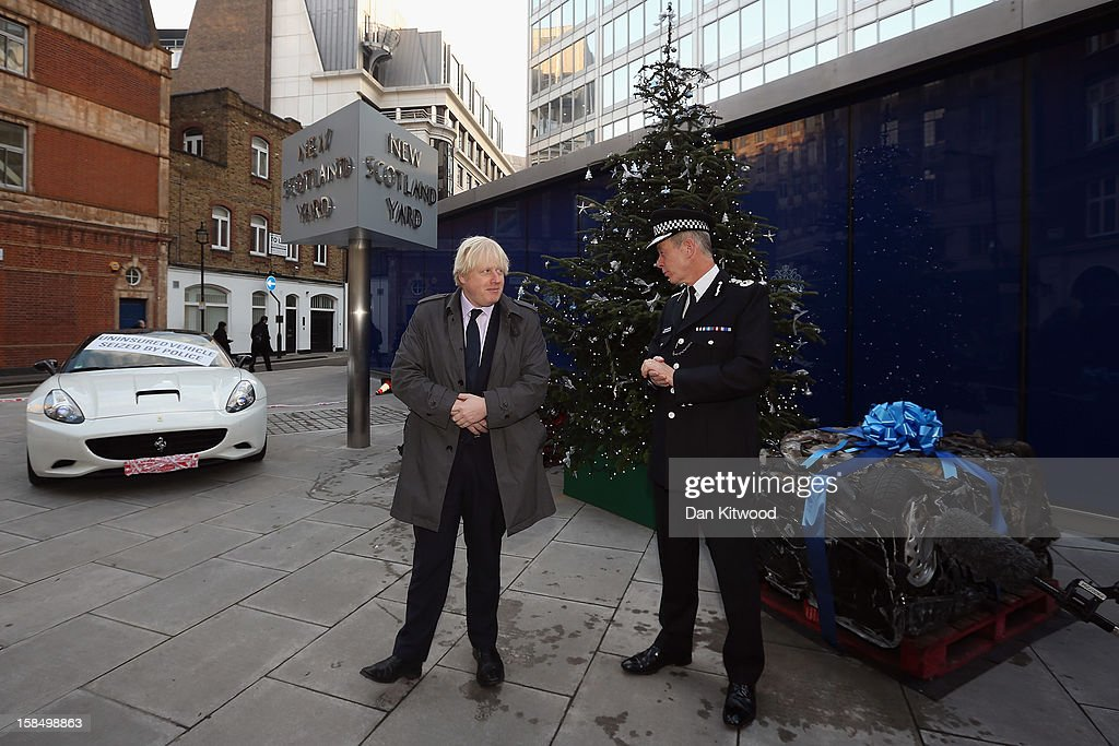 Metropolitan Police Commissioner Bernard Hogan-Howe (R) and the Mayor of London Boris Johnson pose next to a crushed car outside New Scotland Yard on December 18, 2012 in London, England. The photocall was designed to send a message to drivers illegally using London's roads over the Christmas period. The photocall coincides with 'Operation Cubo,' a day involving 1250 police officers in a co-ordinated series of operations targeting illegal drivers across the Capital.