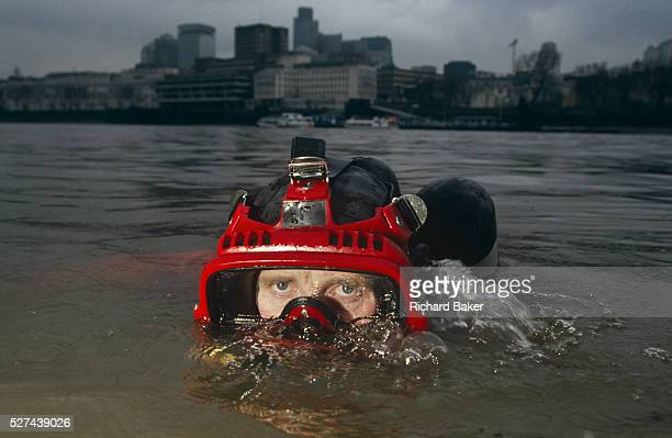 A Metropolitan Police diver surfaces beneath the murky waters of the River Thames in front of the tall buildings of the City of London England...