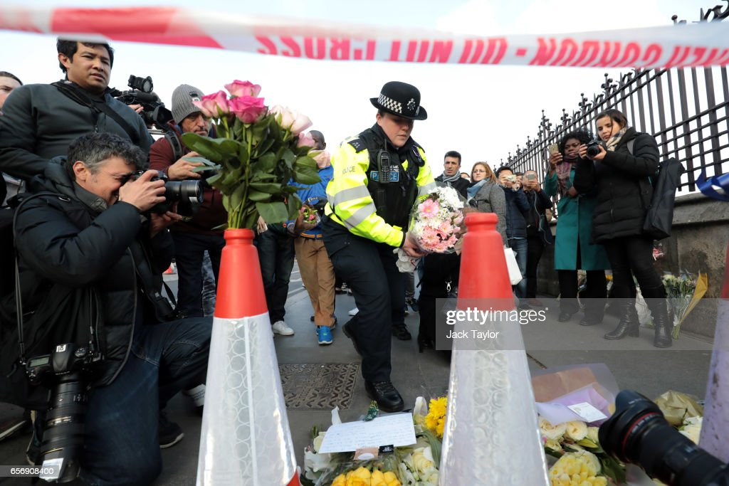 A Metropolitan Police officer arrives with floral tributes near Westminster Bridge following yesterday's attack in which one police officer was killed, on March 23, 2017 in London, England. Four people have been killed and around 40 people injured following yesterday's attack by the Houses of Parliament in Westminster.