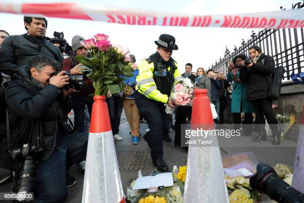 Metropolitan Police officer arrives with floral tributes near Westminster Bridge following yesterday's attack in which one police officer was killed...