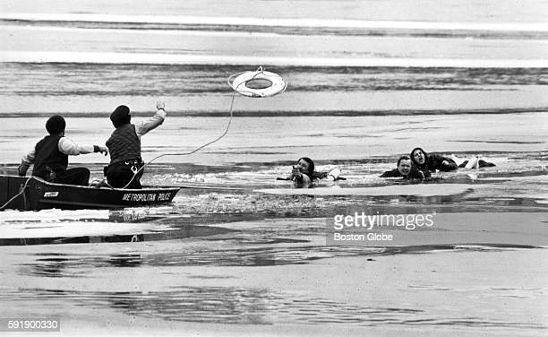 Metropolitan Police officer Michael Janko reaches for a lifesaving ring tossed to him from a boat while fellow officer Michael Hanley clings to a...